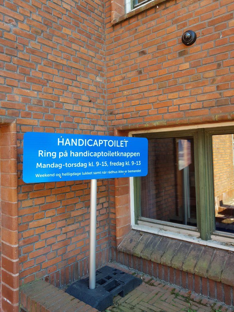 """Et skilt ved rådhusdøren meddeler: """"HANDICAPTOILET -  Ring på handicaptoiletknappen Mandag-torsdag kl. 9-15, fredag kl. 9-13 Weekend og helligdage lukket samt når rådhuset ikke er bemandet"""