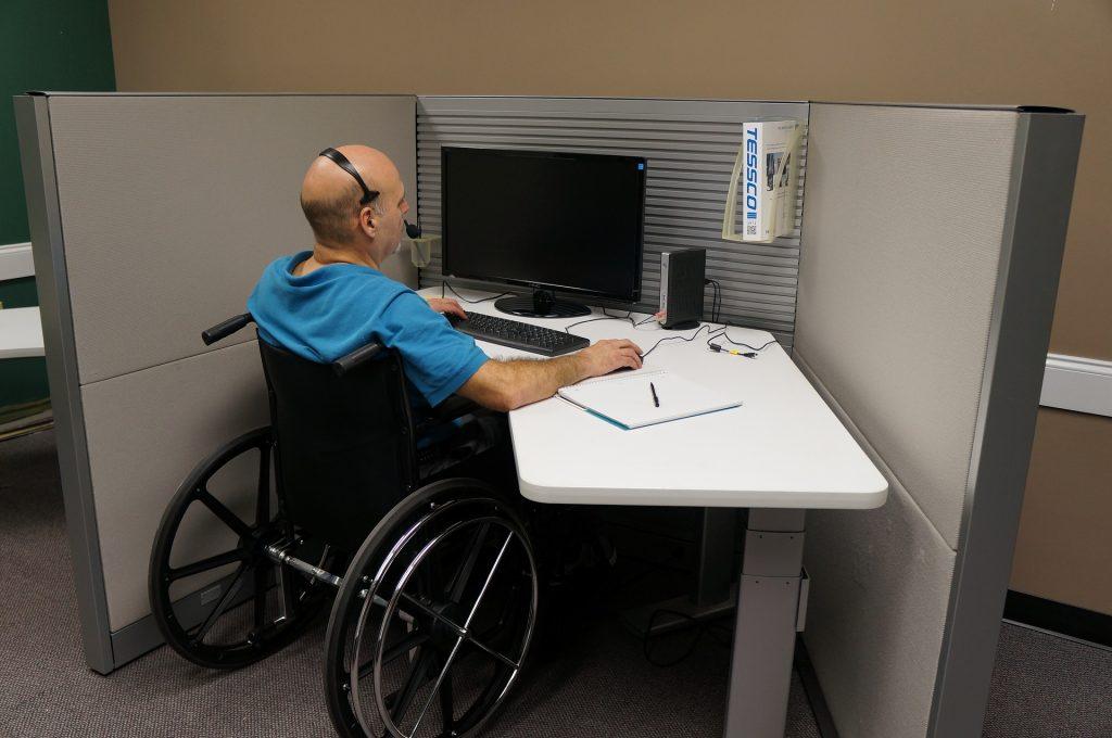 Mand i kørestol ved arbejdsbord med computer.