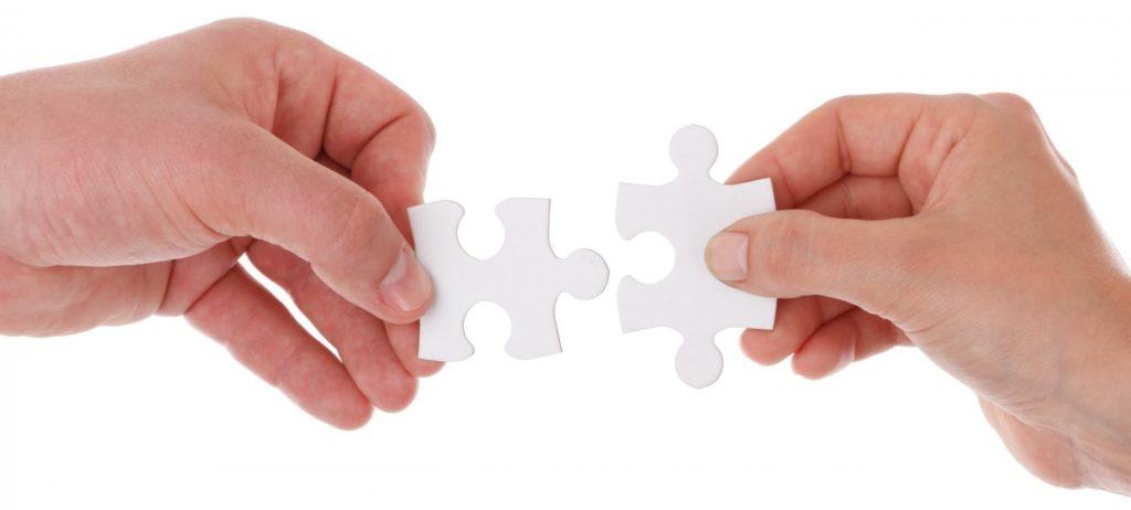 Foto af to hænder, der holder hver sin grå brik fra et puslespil, der passer sammen.